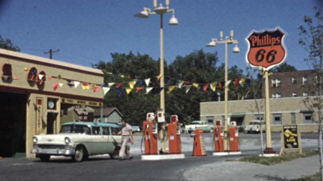 1956 WS Phillips 66 gas station, car pulling up, attendants refueling and washing windows / USA