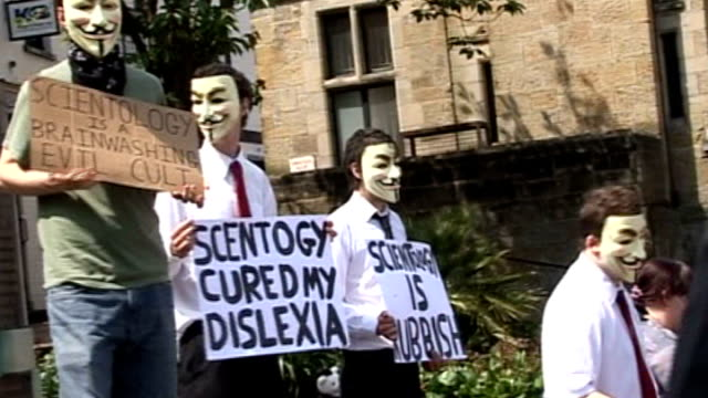 phone call hacked by 'anonymous' group; lib sussex: protesters holding up anti-scientology placards masked protester handing out leaflets - アノニマス点の映像素材/bロール