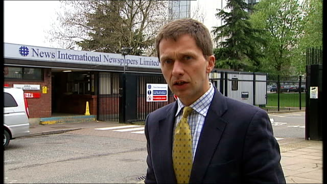 police arrest news of the world reporter and news editor reporter to camera names of news international newspapers on revolving sign mark lewis... - 盗聴点の映像素材/bロール