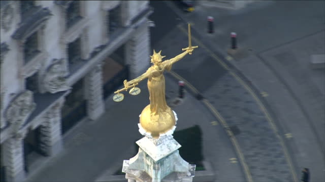 former home secretary's aide had phone hacked; lib / aerial scales of justice statue above old bailey court - 正義の天秤点の映像素材/bロール
