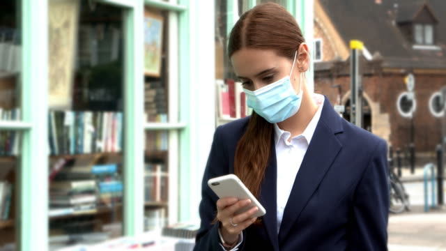 phone message for young woman wearing a face mask in the high street. - phone message stock videos & royalty-free footage