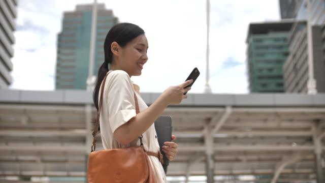 電話メッセージ、街を歩く幸せな若い女性 - 受ける点の映像素材/bロール