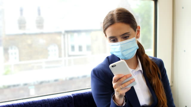 phone message on a train, wearing a mask. young woman and phone. - phone message stock videos & royalty-free footage