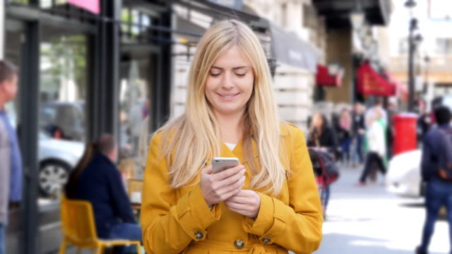 phone message smile, busy city sidewalk. - blonde hair stock videos & royalty-free footage