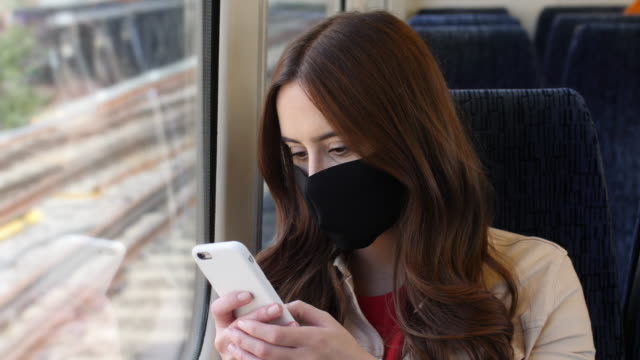 phone message, woman wearing a face mask, train journey. - passenger train stock videos & royalty-free footage