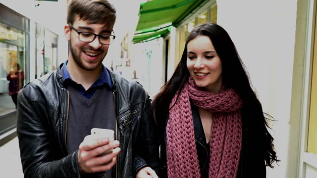 Phone message, young couple walking past shops.