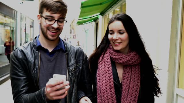 Gesprächsnotiz, junge Paar beim Gehen an Geschäften.