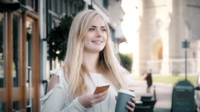 phone message. young woman with a coffee on the go. - blonde hair stock videos & royalty-free footage