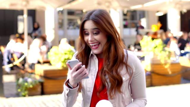 vídeos de stock, filmes e b-roll de celebração do vencedor do telefone. jovem feliz pulando de alegria. - mulheres jovens