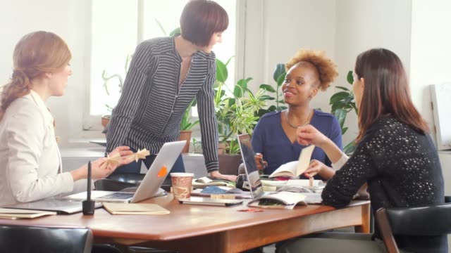 Photo editor explaining art product to female colleagues in board room
