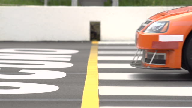 SLO MO. Photo finish profile view as orange stock car crosses the finish line just ahead of two race competitors.