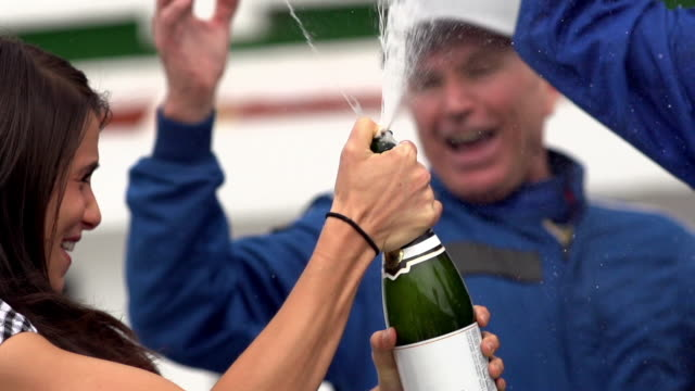Blue racing team celebrates race-track victory with champagne shower