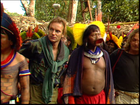Photo flashes go off as press photograph Sting with Raoni Metuktire and other Kayapo Indians in the Amazon