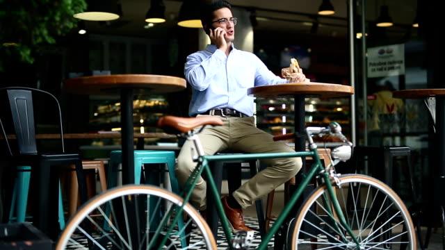 vídeos de stock e filmes b-roll de photo of a handsome man with bike using smartphone - bar local de entretenimento