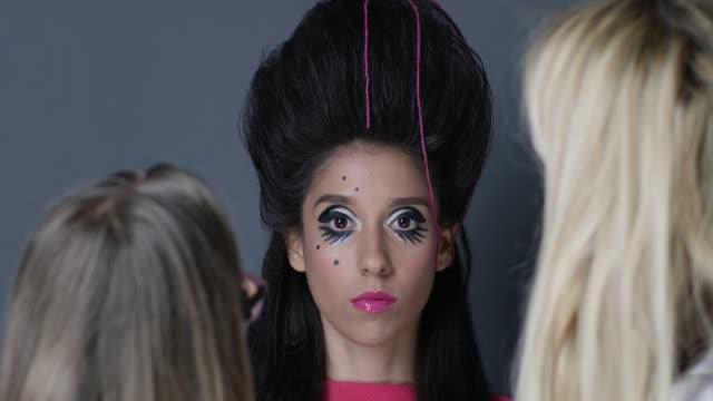 vídeos y material grabado en eventos de stock de sesión de foto/runaway backstage de maquillaje y peluquería que etapa maquillaje y peinado para modelo morena. video de la moda. - esmalte de uñas rojo