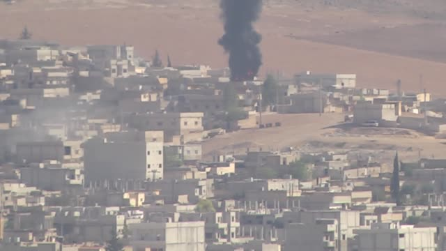 a photograph taken from suruc district of sanliurfa southeastern province of turkey shows smoke rises following airstrikes carried out by the usled... - luftangriff stock-videos und b-roll-filmmaterial