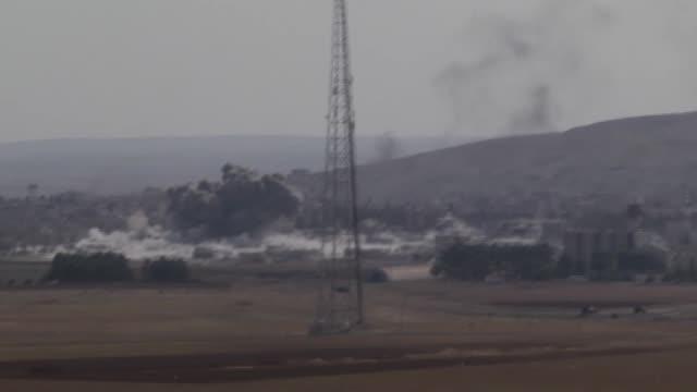 a photograph taken near suruc district of sanliurfa turkey shows smoke rising from the syrian border town of kobani following the usled coalition... - 武力攻撃点の映像素材/bロール