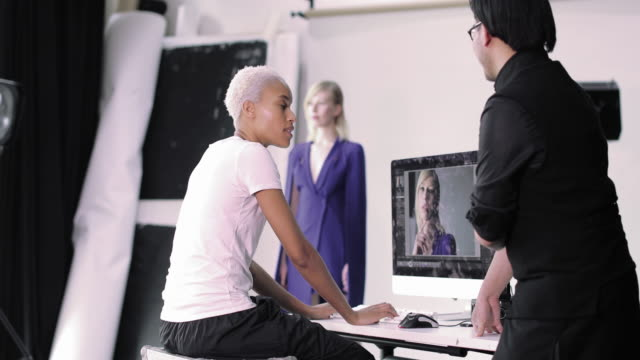 photographer and client reviewing shots on a fashion shoot - fashion show stock videos & royalty-free footage