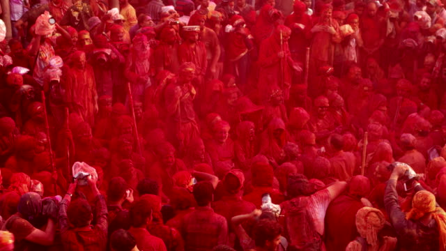 photographer and videographer surround people singing folk songs at holi, festival of colour, while people throwing colors on them - religion stock-videos und b-roll-filmmaterial