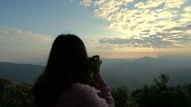 霧、遅い動き、概念の女性ソロ旅行とマウンテン ビューで日の出の写真を撮る写真家アジア女性 - 風景点の映像素材/bロール
