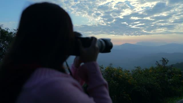 fotografin asiatische frau, die ein foto von sonnenaufgang über der bergansicht mit nebligen, zeitlupe, concept frau solo-reisen - langsam stock-videos und b-roll-filmmaterial