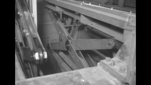 "photographer at right rides upward on mechanical equipment ""from mosler safe co. hamilton, ohio"" / large scissored mechanisms with springs raise and... - 独立宣言点の映像素材/bロール"