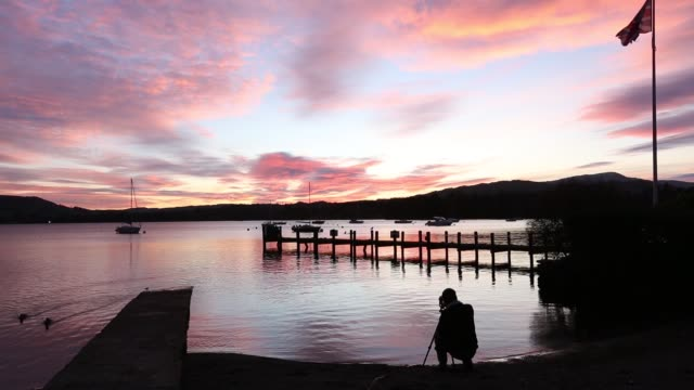 a photographer captures the sunset at waterhead, in ambleside over lake windermere, lake district national park, cumbria, uk. - union jack stock videos & royalty-free footage