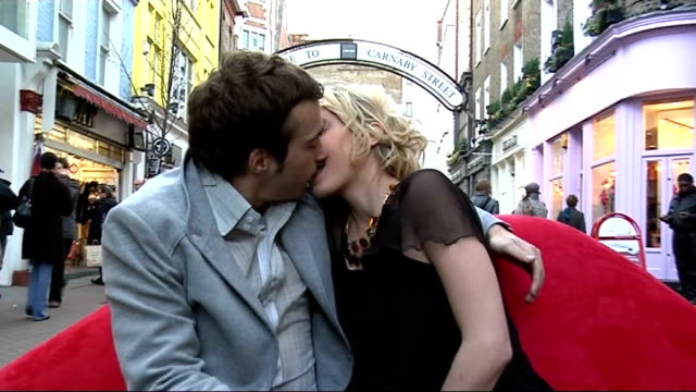photographer encourages public to kiss in carnaby street; **je t'aime music overlaid on following shots sot** models snogging sitting on 'lips' sofa... - labbra video stock e b–roll