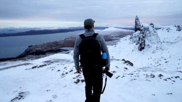 photographer explores rugged snowy highland mountain range - scottish highlands stock videos & royalty-free footage