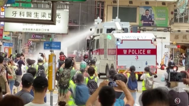 a photographer in hong kong is hit by police water cannon while taking pictures of a small crowd sheltering in a doorway in wan chai - wan chai stock videos & royalty-free footage