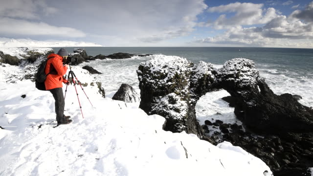 photographer in the snow. snaefellsnes peninsula, iceland. - winter coat stock videos & royalty-free footage