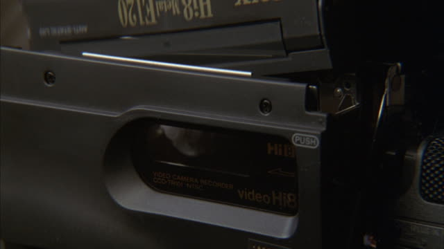 A photographer inserts a tape into a video camera.