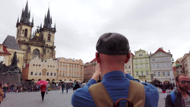 photographer is taking shots of  church of our lady before týn in old town hall tower  in prague in czech republic - astronomical clock prague stock videos and b-roll footage
