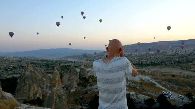 stockvideo's en b-roll-footage met fotograaf is het nemen van foto's van hete lucht ballonnen vliegen over de goreme in cappadocië - ballon