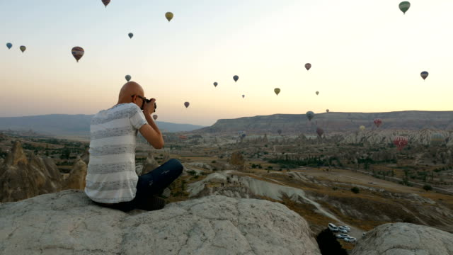 photographer is taking shots of hot air balloons flying over the goreme  at cappadocia - avventura video stock e b–roll