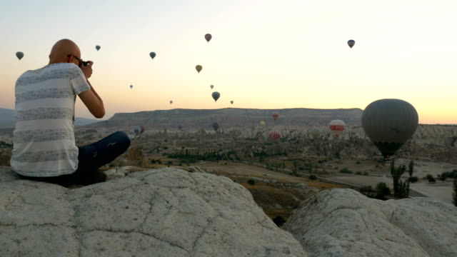 photographer is taking shots of hot air balloons flying over the goreme  at cappadocia - rock hoodoo stock videos and b-roll footage