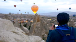 Photographer is taking shots of hot air balloons inflating in Goreme in Cappadocia