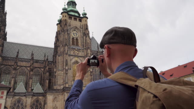 photographer is taking shots of  st. vitus cathedral in prague in czech republic - astronomical clock prague stock videos and b-roll footage