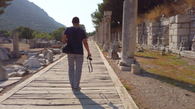 photographer is walking in ephesus ancient city - greece stock videos & royalty-free footage