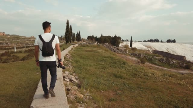 photographer is walking in travertines  in hierapolis , pamukkale - photographer stock videos and b-roll footage