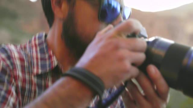 vídeos de stock e filmes b-roll de photographer lifts camera to take shot - temas fotográficos