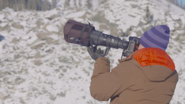 photographer lines up a shot on top of a mountaintop - telephoto lens stock videos and b-roll footage