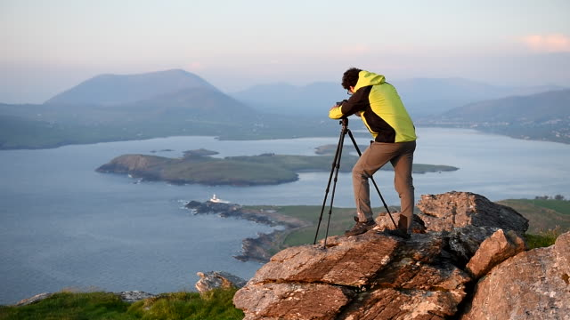 A photographer on top of Geokaun mountain and Fogher Cliffs. Valentia Island, County Kerry, Ireland.