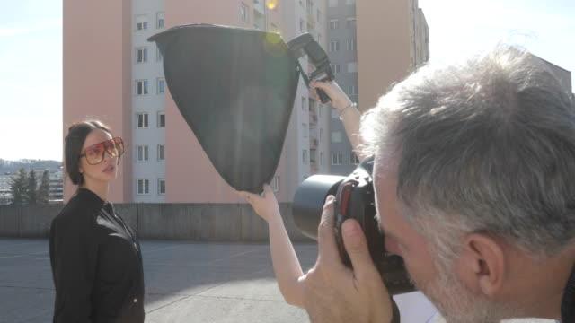 vídeos de stock, filmes e b-roll de fotógrafo fotografando uma mulher bonita ao ar livre em uma cidade - modelo profissional