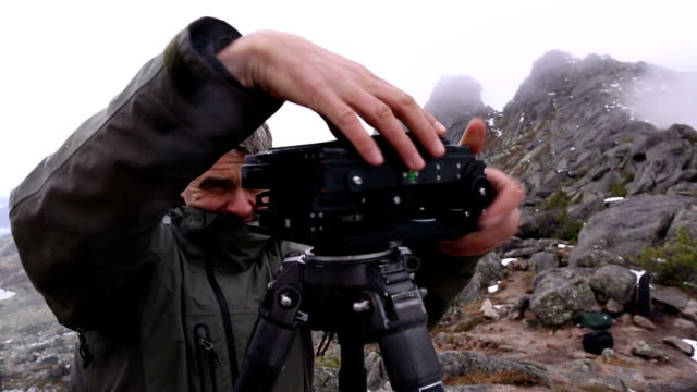 CU Photographer preparing the old school camera to shooting in the mountains.