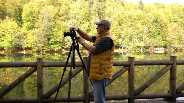 Photographer senior man photographing on the coast of a lake