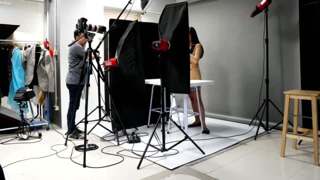 写真家は、タイムラプスで照明器具の背景を持つスタジオルームを設定します - 撮影現場点の映像素材/bロール