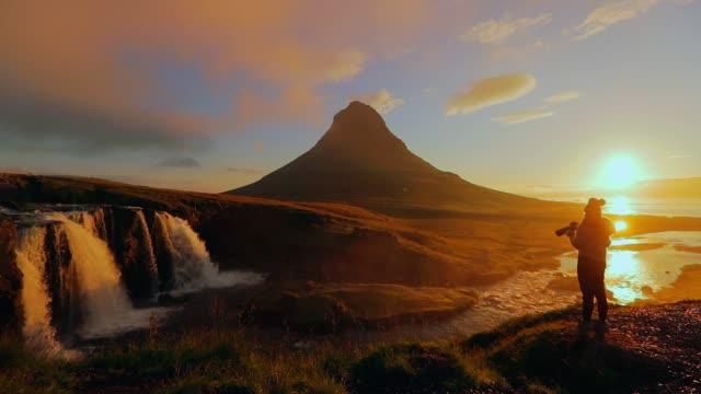 fotograf-shooting kirkjufellsfoss wasserfall am morgen, island - weitwinkel stock-videos und b-roll-filmmaterial