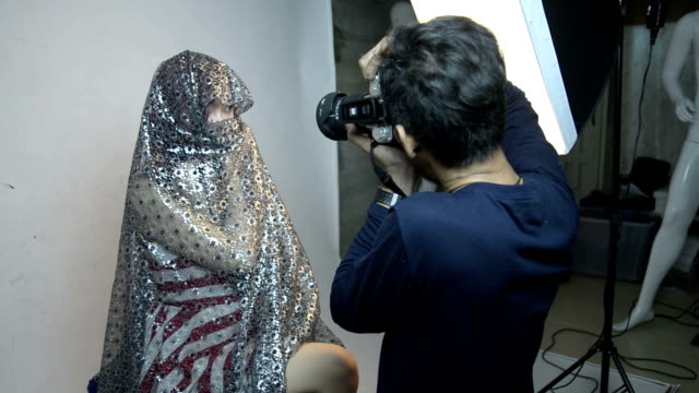 Photographer shooting fashion model in the studio.