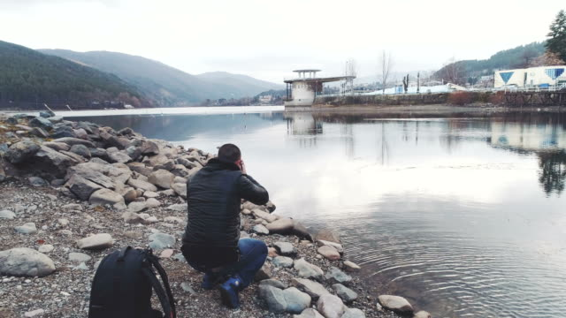 Photographer shooting photographing outdoors near lake drone shot